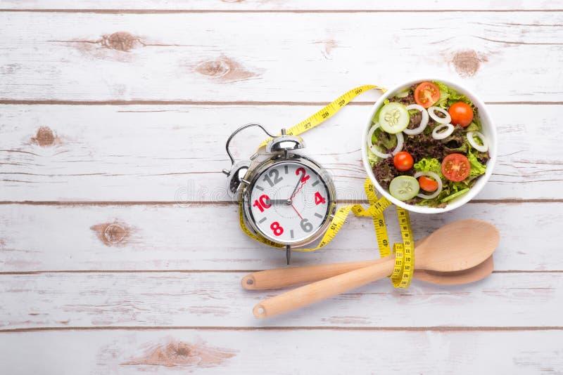 Frischer gesunder Salat und messendes Band auf Holztisch stockbild