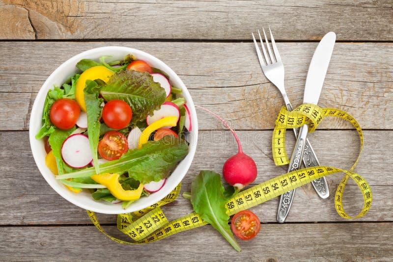 Frischer gesunder Salat und messendes Band Gesunde Nahrung stockbilder