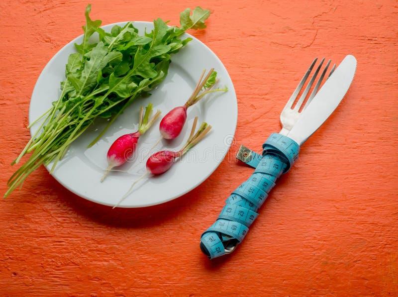 Frischer gesunder Salat und Tischbesteck mit messendem Band auf orange Tabelle Draufsicht des gesunden Lebensmittels stockbild