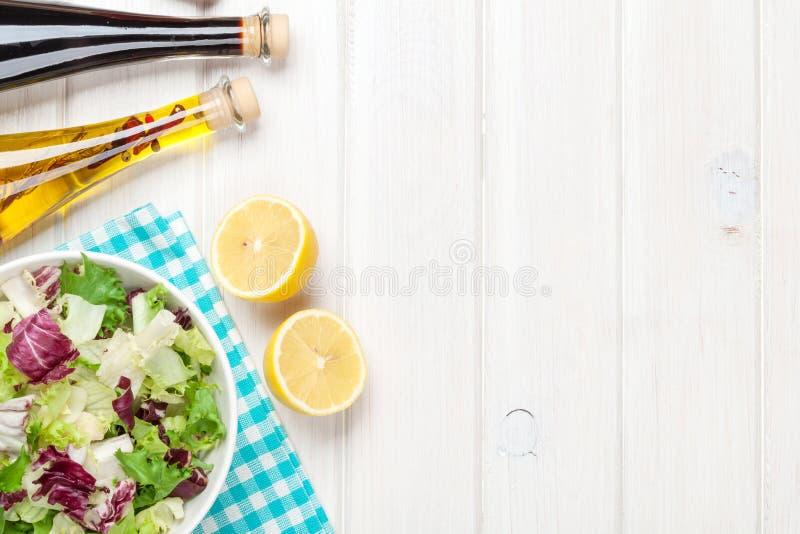 Frischer gesunder Salat und Würzen über weißem Holztisch lizenzfreies stockfoto