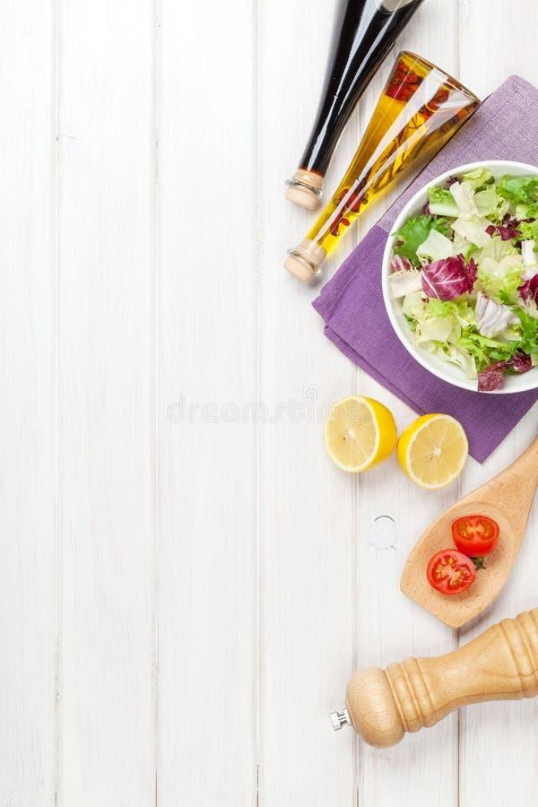 Frischer gesunder Salat und Würzen über weißem Holztisch lizenzfreie stockfotos