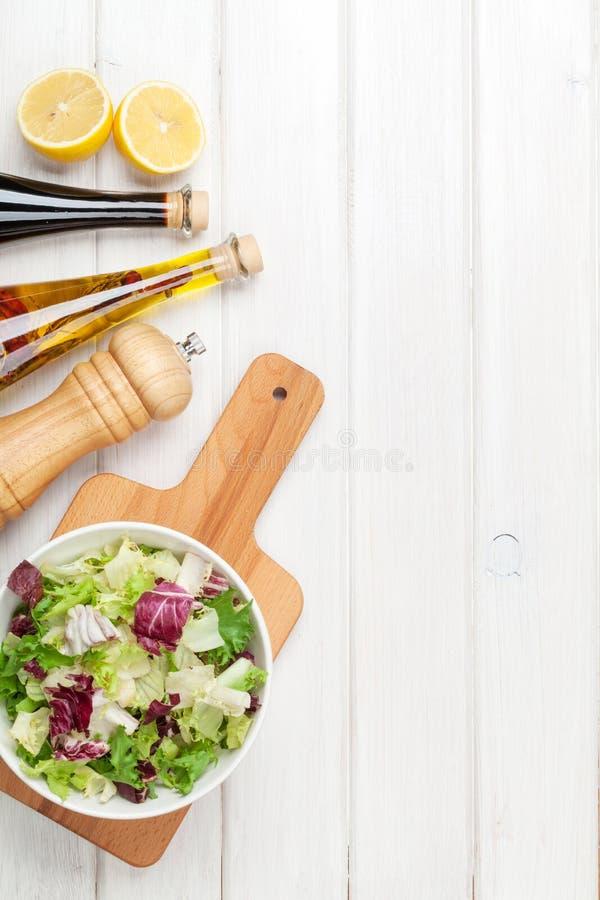 Frischer gesunder Salat und Würzen über weißem Holztisch stockfotografie