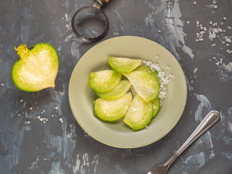 Frischer grüner Rettich geschnitten in Scheibenlügen auf einer keramischen olivgrünen Platte, mit einer Gabel und einer Schälerlü stockbild