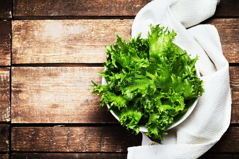 Frischer grüner Salat in einem Teller über hölzernem Hintergrund Diät-Lebensmittel stockbilder