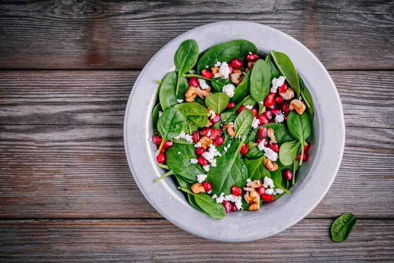 Frischer grüner Salat mit Spinat, Walnüssen, Ziegenkäse und Granatapfel stockbild