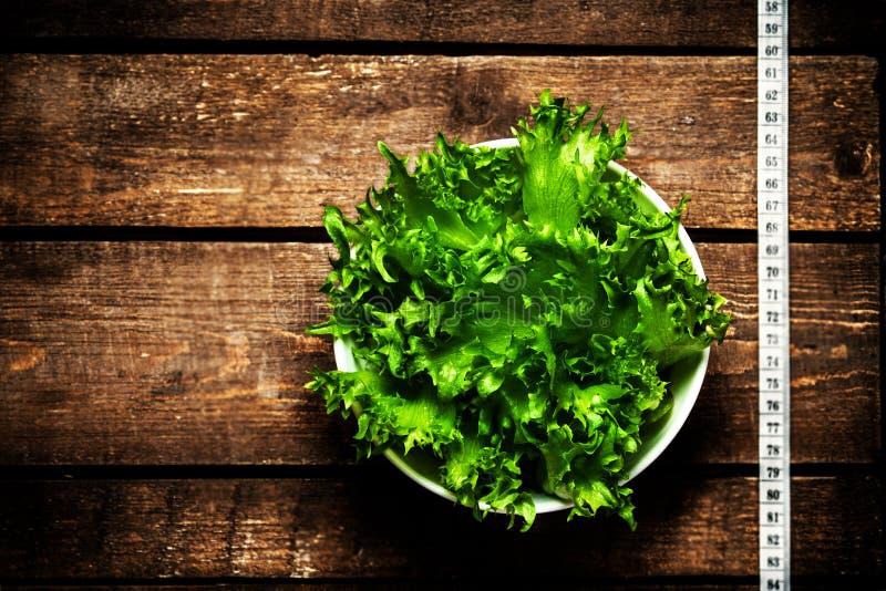 Frischer grüner Salat und messendes Band auf rustikalem hölzernem Hintergrund lizenzfreie stockbilder