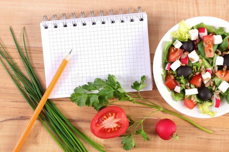 Frischer griechischer Salat mit Gemüse und Notizblock für das Schreiben von Anmerkungen, gesunde Nahrung lizenzfreie stockfotos