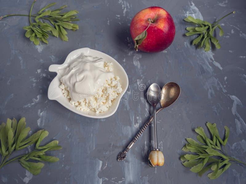 Frischer Hüttenkäse mit Sauerrahm, roter Apfel, ein Teelöffel stockfotografie