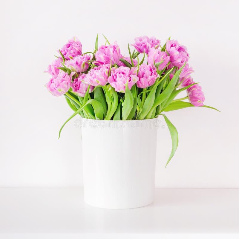 Frischer heller Blumenstrauß der rosa Tulpe im weißen Eimer Schöne Grußkarte Frühlingsfeiertagskonzept Copyspace Platz für Ihr te stockbild