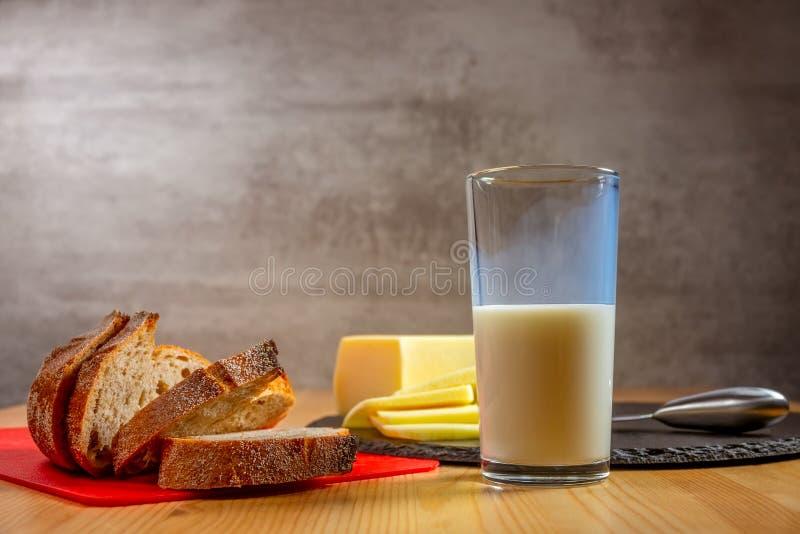 Frischer Käse, Brot und Milchglas lizenzfreie stockbilder