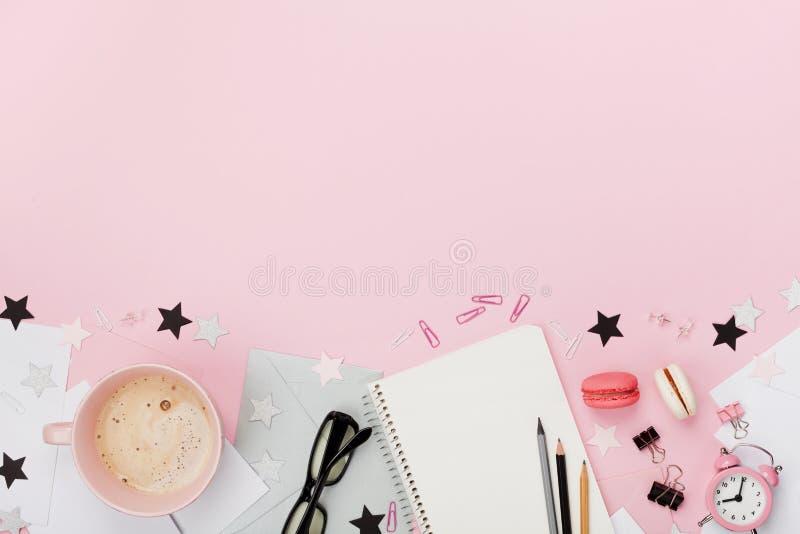 Frischer Kaffee, macaron, Bürozubehör, Wecker und Notizbuch auf rosa Pastelltischplatteansicht flache Lageart Gemütliches Frühstü lizenzfreie stockbilder