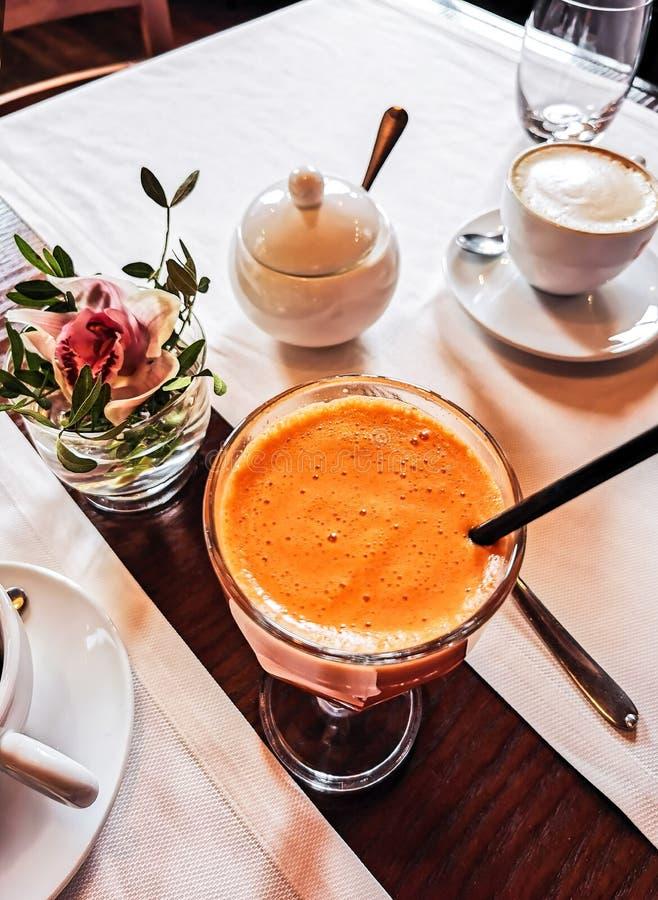 Frischer Karottensaft der Draufsicht in einem Glas mit einem Stroh auf dem Tisch der Hintergrund von Tasse Kaffees stockfotos
