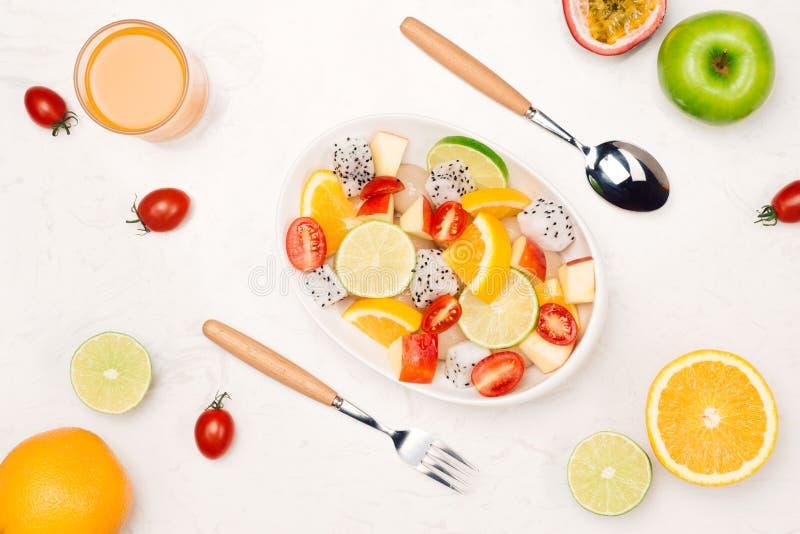 Frischer Mischobstsalat, der in eine Schüssel Salat fällt lizenzfreie stockfotografie
