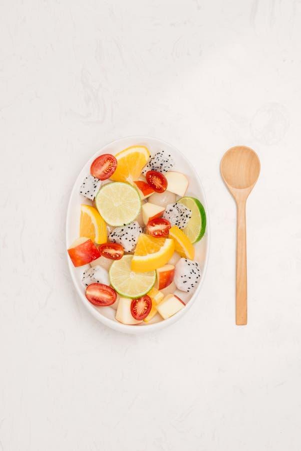 Frischer Mischobstsalat, der in eine Schüssel Salat fällt lizenzfreie stockbilder
