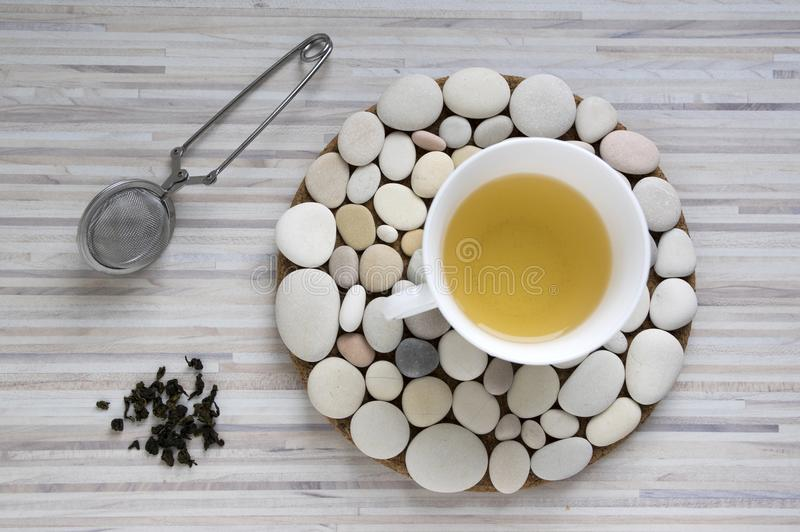 Frischer oolong Tee im weißen Topf auf Steinen kreisen Behälter auf Licht gestreifter Tabelle ein stockbilder