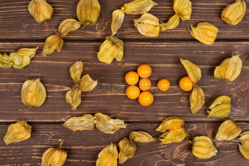 Frischer orange Physalis auf braunem Holz stockfotos