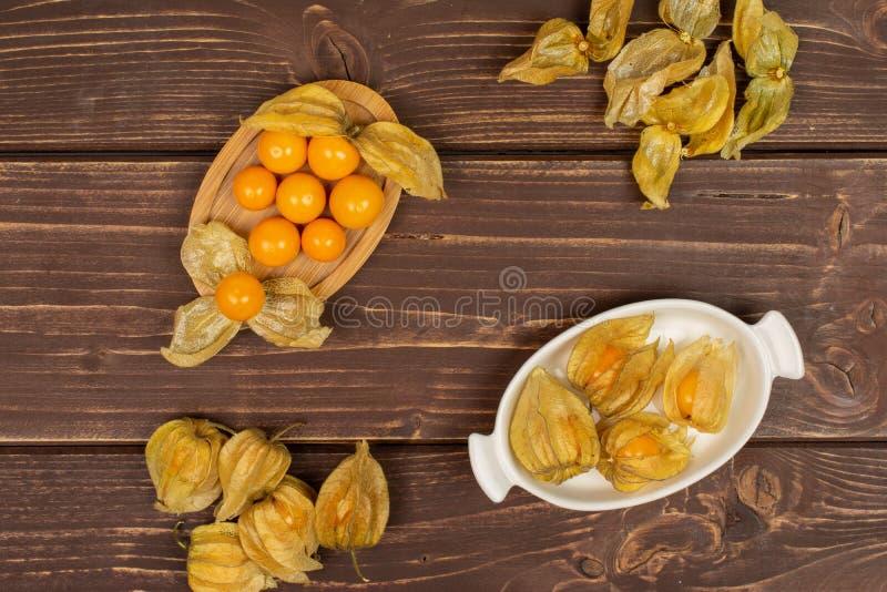 Frischer orange Physalis auf braunem Holz stockbild