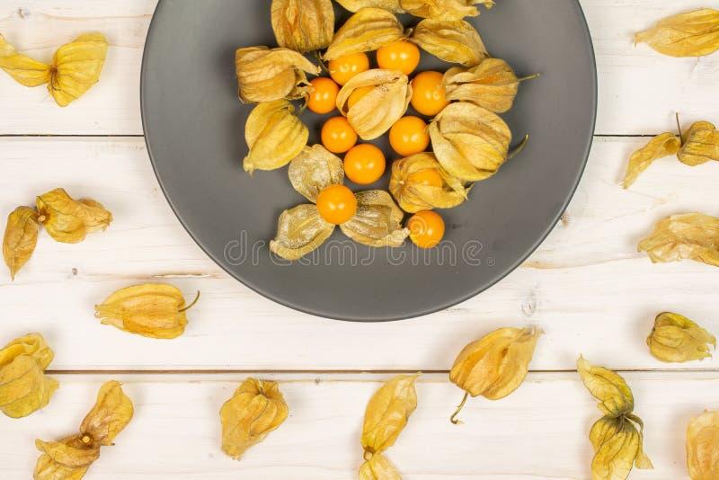 Frischer orange Physalis auf grauem Holz stockfotos