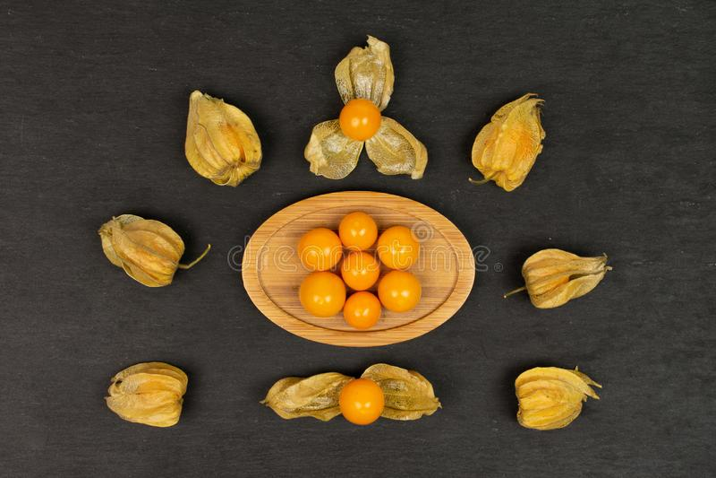 Frischer orange Physalis auf grauem Stein stockbilder