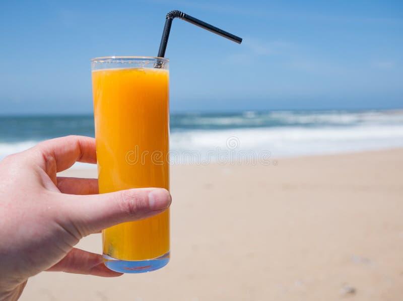 Frischer Orangensaft auf goldenem sandigem Strand mit blauem Himmel stockbilder