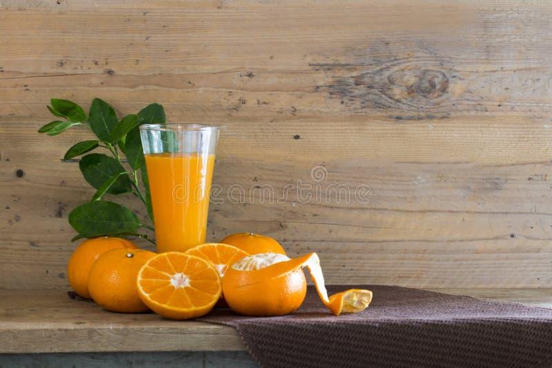 Frischer Orangensaft im Glas auf Holz zu kreativem für Design lizenzfreie stockbilder