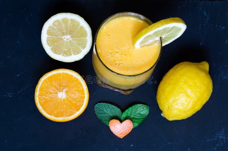 Frischer Orangensaft im Glas, Zitrone, orange auf schwarzem Stein-backgr lizenzfreie stockfotos