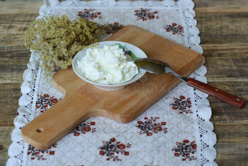Frischer organischer handgemachter Käse, der im Seihtuch und in der Weinleseplatte hängt stockbild