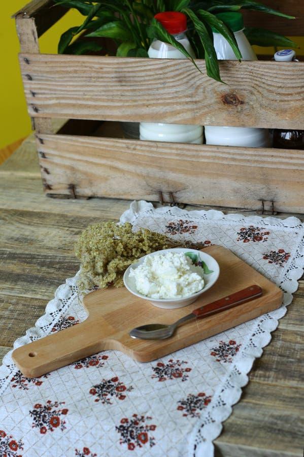 Frischer organischer handgemachter Käse, der im Seihtuch und in der Weinleseplatte hängt lizenzfreie stockfotografie