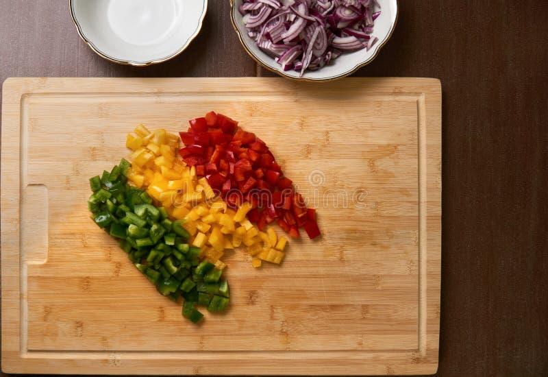 Frischer Paprika Cutted bessert Spitzen ansehen unten auf einem Bambusschneidebrett mit cutted Zwiebeln aus Ohne Hand stockbild