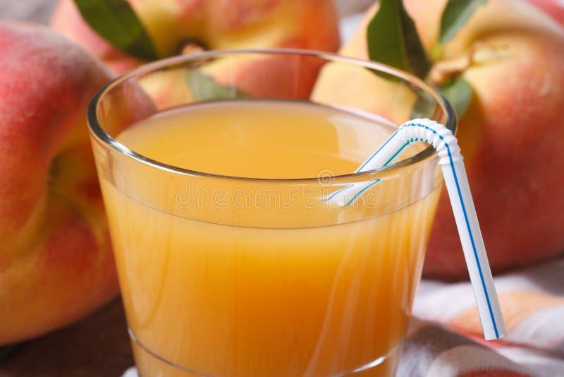 Frischer Pfirsichsaft in der Glasnahaufnahme auf einem Hintergrund der reifen Frucht lizenzfreie stockfotos