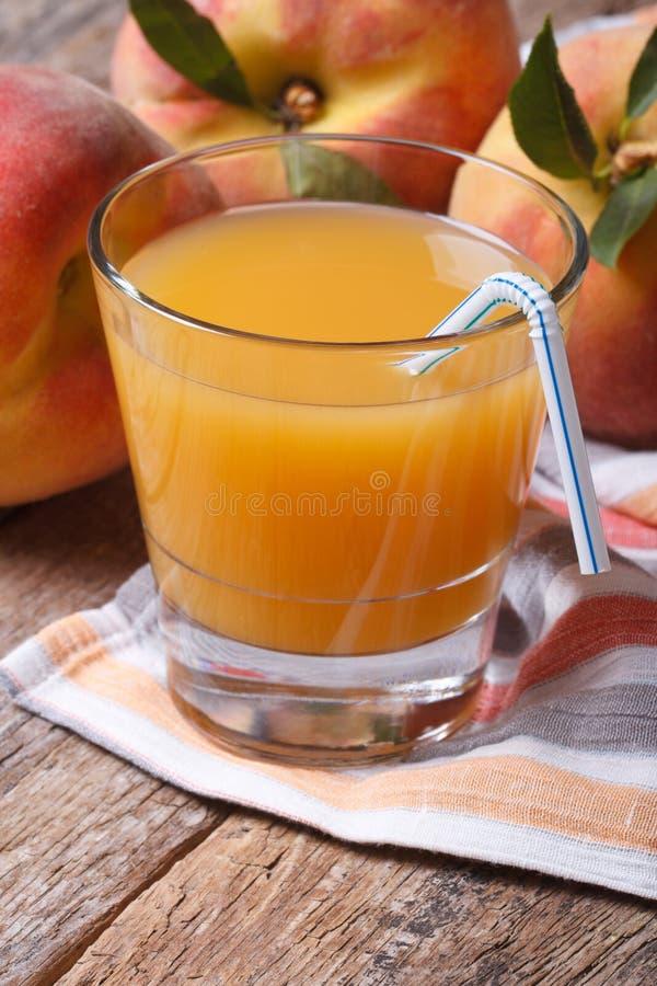 Frischer Pfirsichsaft in einer Nahaufnahmevertikale des Glases auf dem Tisch stockbilder