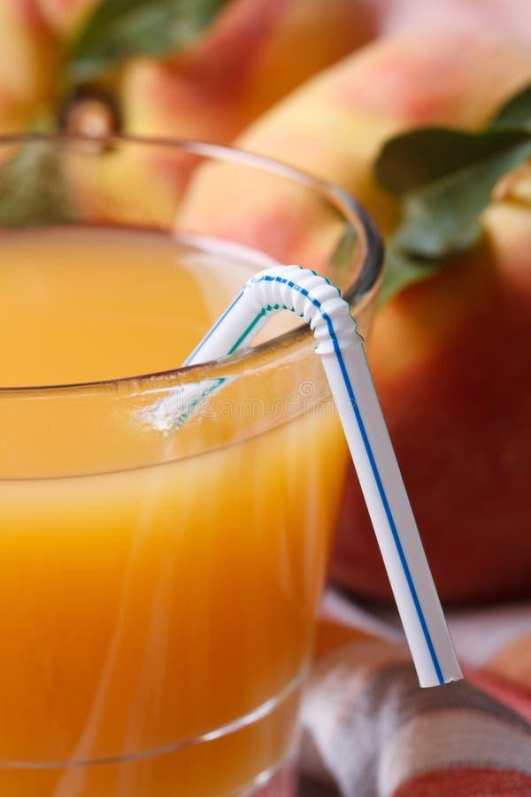 Frischer Pfirsichsaft im Glasmakro- und in der reifen Frucht vertikal stockbilder