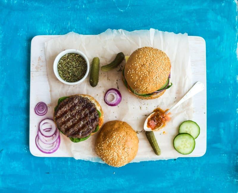 Frischer Rindfleischburger mit Käse, Gemüse, würzige Tomatensauce auf Papier- und weißem Umhüllungsbrett, blauer hölzerner Hinter stockbilder