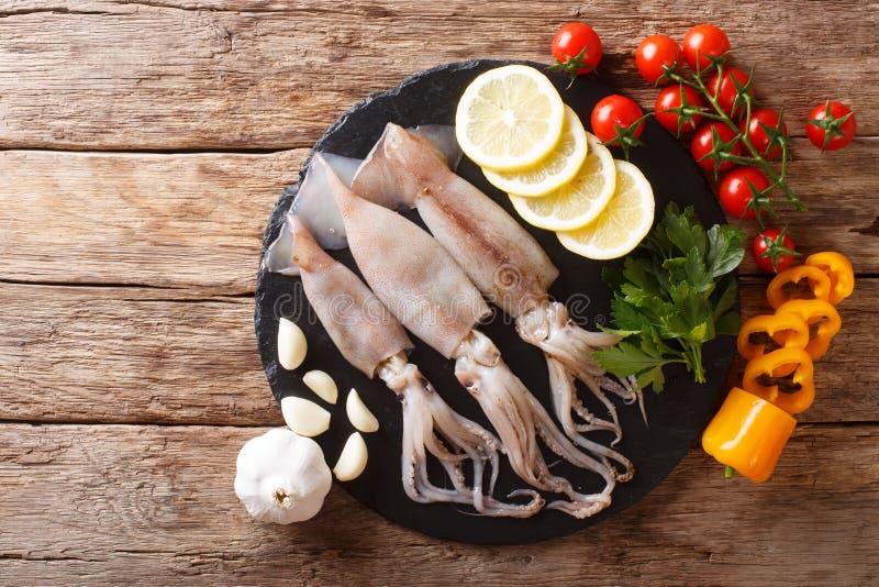 Frischer roher Kalmar mit Tentakeln Nahaufnahme und Gemüsebestandteilen stockfotografie