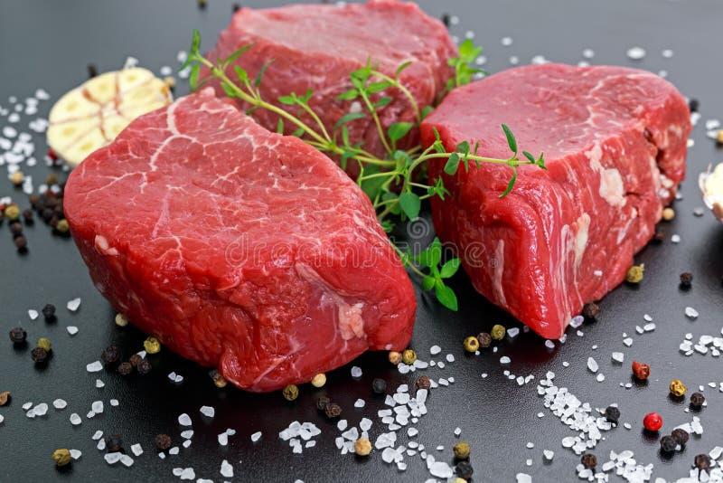 Frischer roher Rindfleischsteak Mignon, mit Salz, Pfefferkörner, Thymian, Knoblauch kochfertig lizenzfreie stockfotografie