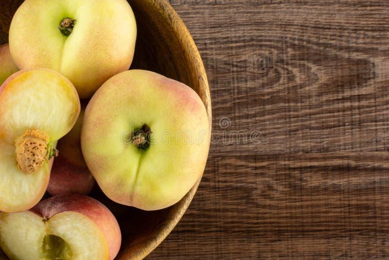 Frischer roher Saturn-Pfirsich auf braunem Holz stockbild