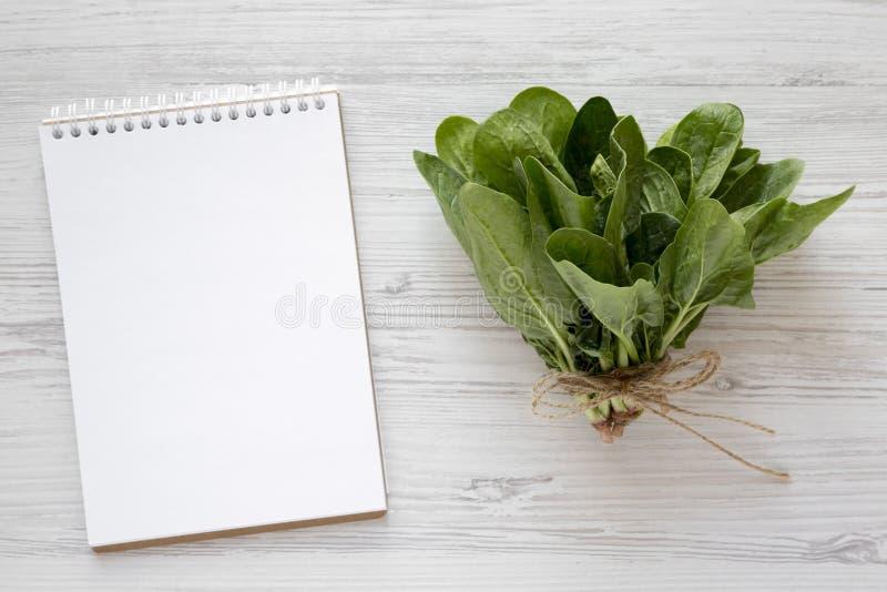 Frischer roher Spinat und leerer Notizblock auf einem weißen hölzernen Hintergrund Flache Lage, obenliegend, von oben Kopieren Si lizenzfreie stockbilder