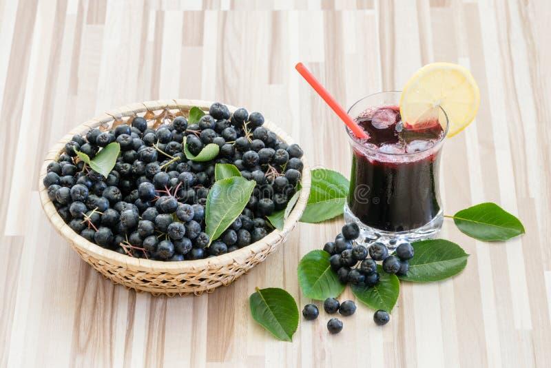 Frischer Saft von Chokeberry oder von Aronia-melanocarpa im Glas mit Eis, Zitrone und Stroh lizenzfreie stockbilder