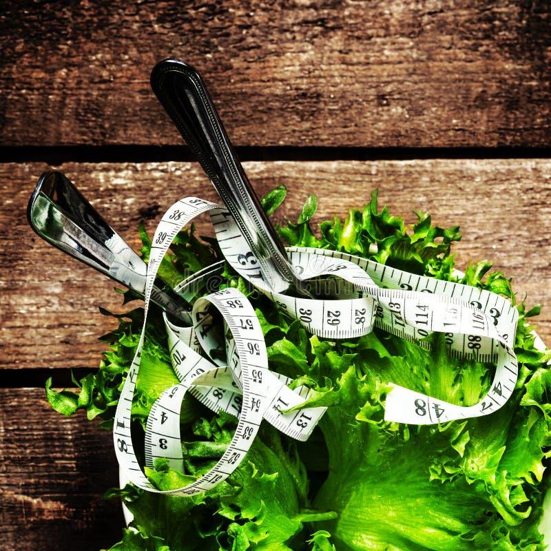 Frischer Salat in einer Schüssel mit messendem Band über Holztischesprit stockbild