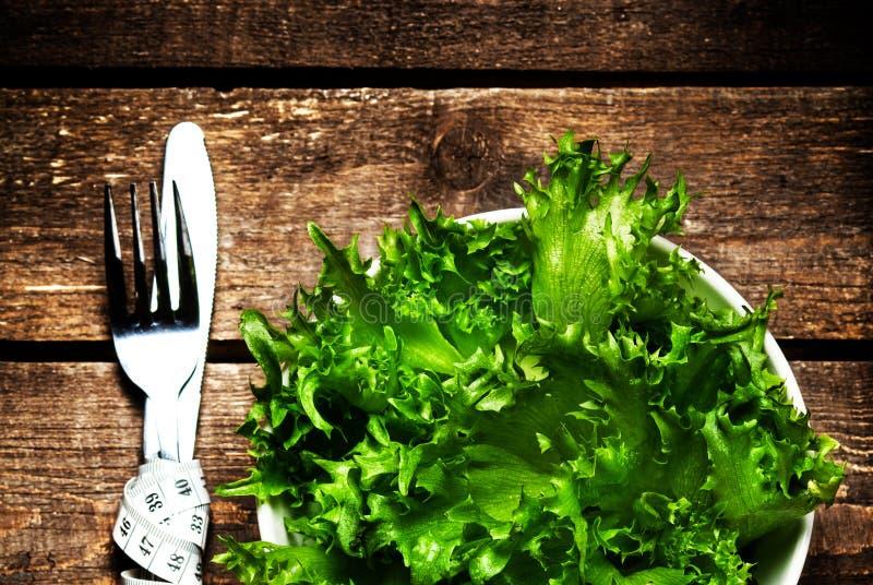 Frischer Salat in einer Schüssel mit messendem Band über Holztischesprit stockfotos