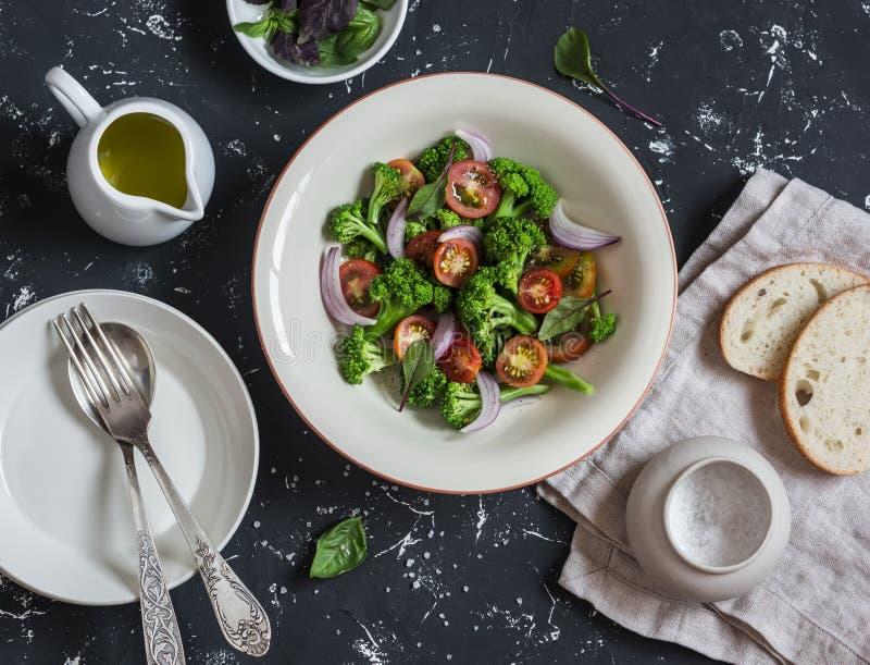 Frischer Salat mit Brokkoli und Tomaten auf einem dunklen Hintergrund lizenzfreies stockfoto
