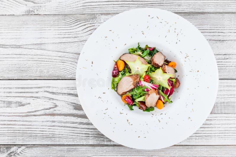 Frischer Salat mit der Hühnerbrust, Arugula, Kopfsalat, Blumenkohl, Physalis und Carambola auf Platte auf hölzernem Hintergrundab stockfotografie