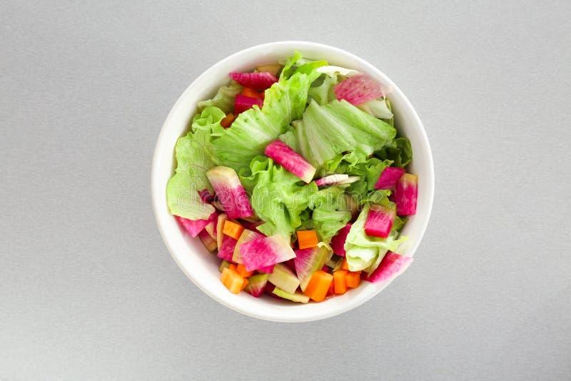 Frischer Salat mit geschnittenem Rettich und Kopfsalat in der Schüssel auf hellem Hintergrund, Draufsicht lizenzfreie stockbilder