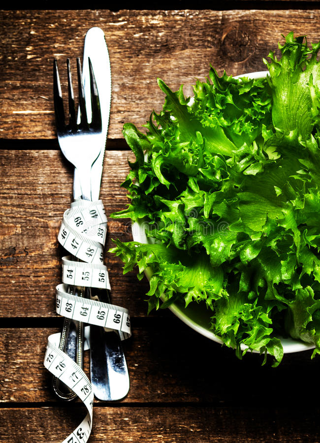 Frischer Salat mit messendem Band der Eignung auf hölzernem Hintergrundesprit lizenzfreie stockfotografie