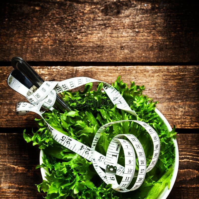 Frischer Salat mit messendem Band der Eignung auf hölzernem Hintergrundesprit stockfoto