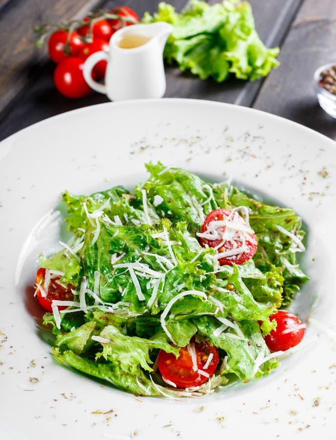 Frischer Salat mit Mischgrüns, Kirschtomaten, Parmesankäseparmesankäse auf hölzernem Hintergrund stockfoto