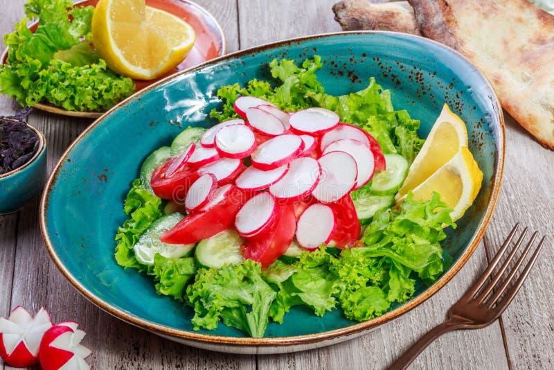 Frischer Salat mit Rettich, Kirschtomaten, Gurke, Kopfsalat und Glas Wein auf hölzernem Hintergrund stockbilder