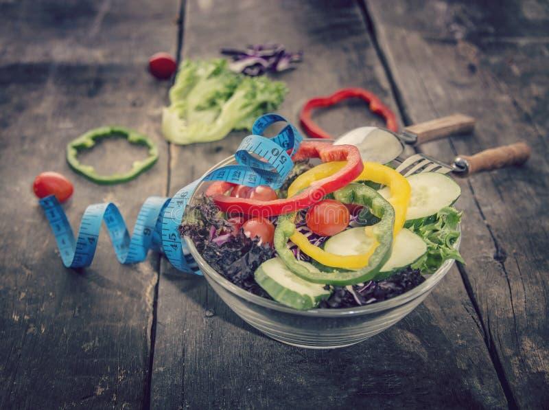 Frischer Salat und messendes Band auf Holztisch Mischgrüns, t lizenzfreie stockfotografie