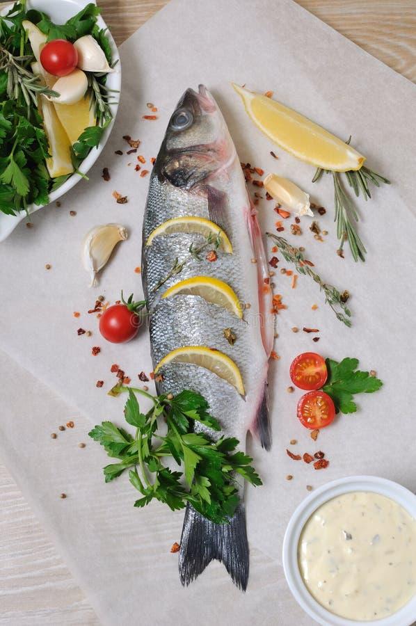 Frischer Seebarsch mit Zitrone und Gewürzen lizenzfreie stockfotos