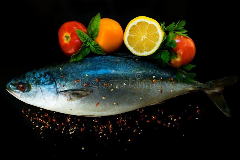 Frischer Seefischthunfisch herein mit Gemüse und Gewürzen auf einem schwarzen Hintergrund stockbilder